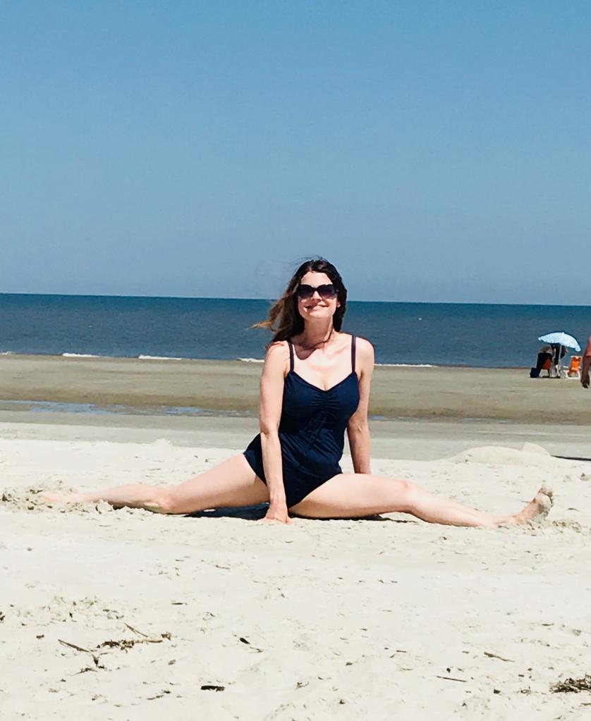 Yoga Teacher Kimberly is doing a split on the beach.